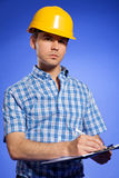 Architect in yellow hardhat writing on clipboard Stock Image