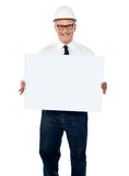 Architecte aîné retenant le panneau-réclame blanc Photo libre de droits