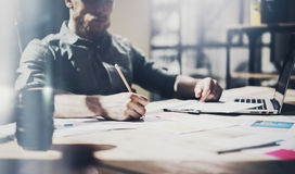Architecte barbu de photo travaillant avec le nouveau projet Carnet générique de conception sur la table en bois Analysez les pla photo libre de droits