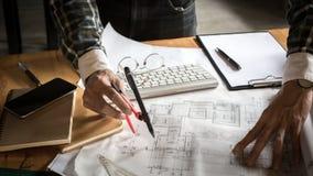 Architecte créatif projetant sur les grands dessins dans le lo foncé images stock