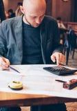 Architecte de concepteur d'ingénieur d'homme lisant des dessins à la table en café image libre de droits