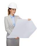 Architecte de sourire dans le casque blanc avec des modèles Photos stock