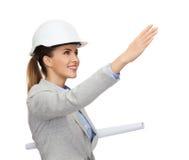 Architecte de sourire dans le casque blanc avec des modèles Images libres de droits