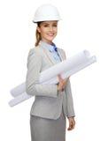 Architecte de sourire dans le casque blanc avec des modèles Images stock