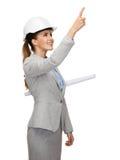 Architecte de sourire dans le casque blanc avec des modèles Image stock