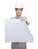 Architecte de sourire dans le casque blanc avec des modèles Image libre de droits