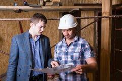Architecte et agent de maîtrise Inspecting Building Plans Photo stock