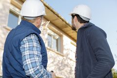 Architecte et maçon inspectant la maison extérieure image libre de droits