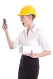 Architecte fâchée de femme d'affaires dans des cris jaunes de casque de constructeur Photographie stock