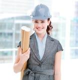 Architecte féminin gai avec le casque antichoc et les plans Image stock