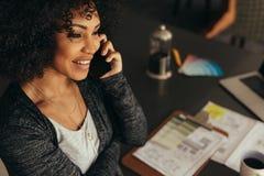 Architecte féminin parlant avec le client au-dessus du téléphone images stock