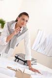 Architecte féminin travaillant au crayon lecteur de fixation de bureau Images stock