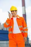 Architecte heureux portant les vêtements de travail réfléchis communiquant sur le talkie - walkie au site Photo stock