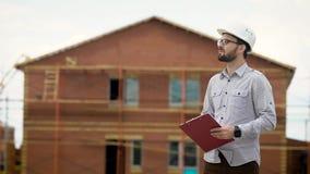 Architecte masculin avec le presse-papiers se tenant sur le chantier de construction près de la maison clips vidéos