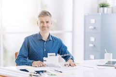 Architecte professionnel posant dans le bureau avec un modèle architectural d'un bâtiment contemporain image stock
