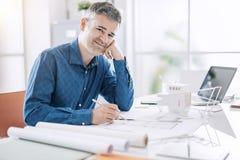 Architecte professionnel sûr posant dans son bureau et souriant à la caméra, il s'assied au bureau et travaille à un bâtiment photographie stock