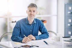 Architecte professionnel s'asseyant au bureau et travaillant, il vérifie un modèle, une ingénierie et une architecture de projet photo libre de droits