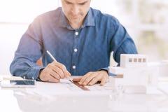 Architecte professionnel travaillant au bureau, il dessine avec une règle sur un projet d'ébauche, architecture et machine le con photos stock