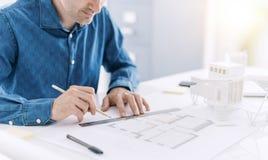 Architecte professionnel travaillant au bureau, il est dessinant et faisant des mesures sur un modèle de projet, conception et photos libres de droits