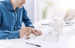 Architecte professionnel travaillant au bureau, il est dessinant et faisant des mesures sur un modèle de projet, conception et photographie stock
