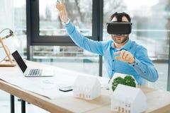 Architecte raidi agréable à l'aide du casque de VR au travail photographie stock