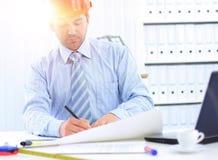 Architecte regardant fonctionnant dans le bureau le bureau image stock