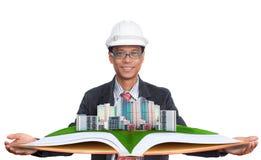 Architecte tenant le champ vert avec le bâtiment moderne ci-dessus images stock