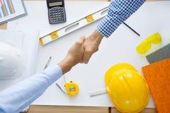 Architecten die met blauwdrukken werken, inspecterend werkplaats engin stock foto