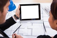 Architecten met digitale tablet die aan blauwdruk werken Stock Fotografie