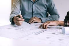Architecten of techniek die met blauwdrukken werken en project bespreken samen op de vergadering in het bureau royalty-vrije stock afbeelding