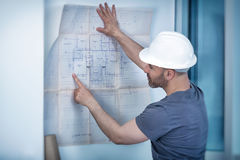 Architectenbouwer die lay-outplan van de ruimten bestuderen Royalty-vrije Stock Foto's