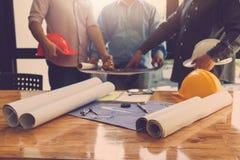 Architectenconcept, Architecten die met blauwdrukken in het bureau werken Stock Foto