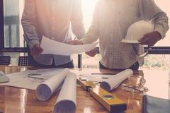 Architectenconcept, Architecten die met blauwdrukken in het bureau werken Stock Afbeelding