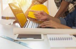 Architecteningenieur die laptop voor het werken met gele helm a met behulp van stock fotografie