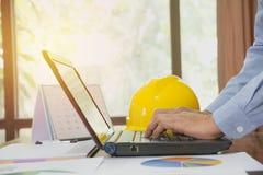 Architecteningenieur die laptop voor het werken met gele helm o met behulp van stock foto's