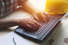 Architecteningenieur die laptop voor het werken met gele helm o met behulp van stock foto