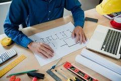 Architectenmens die met blauwdrukken werken stock afbeeldingen