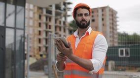 Architectenmens die met tablet op de bouwwerf lopen en het plan van het regelingsproject analyseren Buiten, langzame motie stock footage