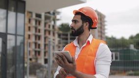 Architectenmens die met tablet op de bouwwerf lopen en het plan van het regelingsproject analyseren Buiten, langzame motie stock video