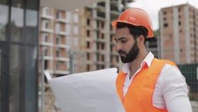 Architectenmens die op de bouwwerf lopen en het plan van het regelingsproject analyseren Buiten, langzame motie stock video