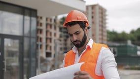 Architectenmens die op de bouwwerf lopen en het plan van het regelingsproject analyseren Buiten, langzame motie stock videobeelden