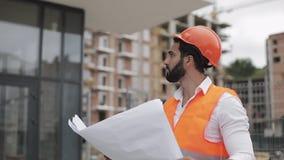 Architectenmens die op de bouwwerf lopen en het plan van het regelingsproject analyseren Buiten, langzame motie stock footage