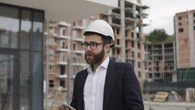 Architectenmens die pak dragen die met tablet op de bouwwerf lopen en het plan van het regelingsproject analyseren stock video