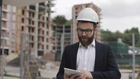 Architectenmens die pak dragen die met tablet op de bouwwerf lopen en het plan van het regelingsproject analyseren stock footage