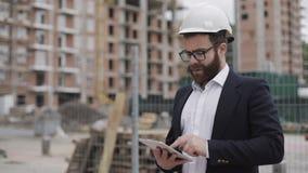 Architectenmens die pak dragen die zich met tablet op de bouwwerf bevinden en het plan van het regelingsproject analyseren stock footage