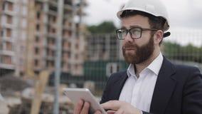 Architectenmens die pak dragen die zich met tablet op de bouwwerf bevinden en het plan van het regelingsproject analyseren stock videobeelden