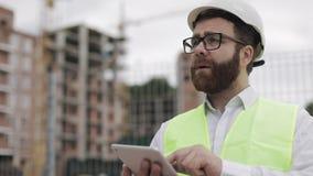 Architectenmens die zich met tablet op de bouwwerf bevinden en het plan van het regelingsproject analyseren Buiten, langzame moti stock footage