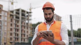 Architectenmens die zich met tablet op de bouwwerf bevinden en het plan van het regelingsproject analyseren Buiten, langzame moti stock videobeelden