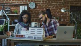 Architectenontwerpers die met miniatuur van installatie coworking stock footage