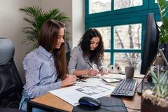 Architectes belles de femmes dans des chemises bleues fonctionnant avec le palatte de couleur pour choisir la conception et les c photos stock